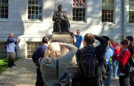 People photographed the John Harvard statue at Harvard University.